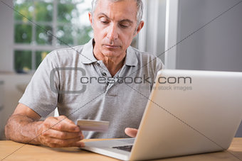Thoughtful mature man using his laptop