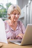 Mature woman touching her laptop