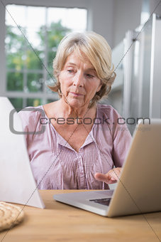 Focused mature woman using her laptop