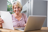 Happy mature woman using her laptop