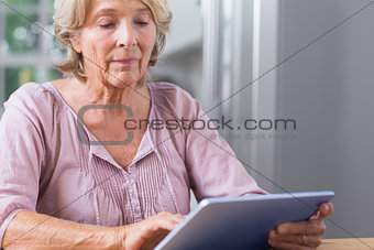 Mature woman touching her digital tablet