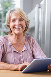 Happy mature woman using her digital tablet