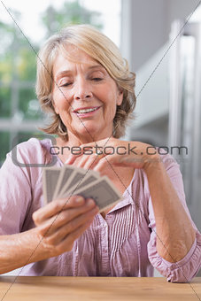 Happy woman playing cards