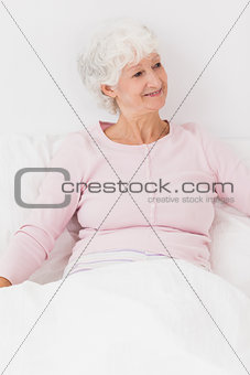 Happy woman sitting in bed
