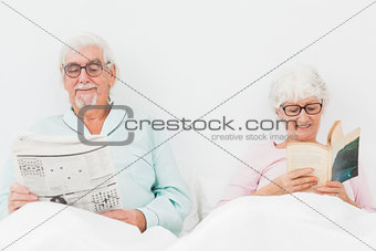 Happy couple reading in bed