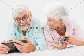 Happy husband and wife reading in bed