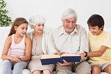 Grandparents reading book with grandchlidren