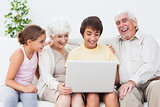 Grandparents and grandchildren using laptop