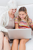 Smiling girl using laptop with granny