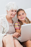 Happy girl using laptop with granny