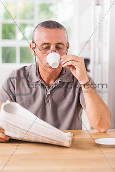 Man reading newspaper and drinking espresso