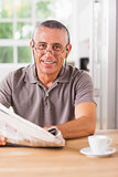 Smiling man reading a newspaper