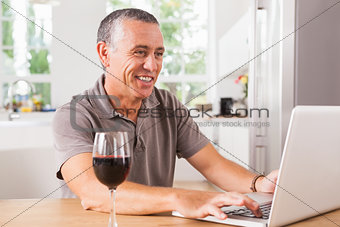 Happy man using laptop with glass of red wine