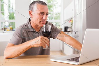 Smiling man drinking red wine and looking at laptop