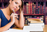 Woman thinking with pen and book in library