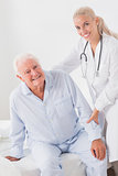 Smiling doctor helping man to sit up