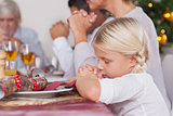 Family saying grace before dinner