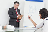 Businessman writing on clipboard in office
