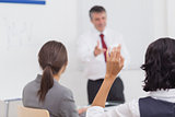 Businessman pointing to his colleague raising her hand