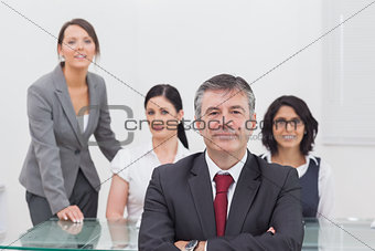 Portrait of happy businessman with team