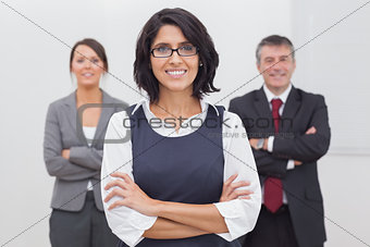 Three businesspeople folding their arms