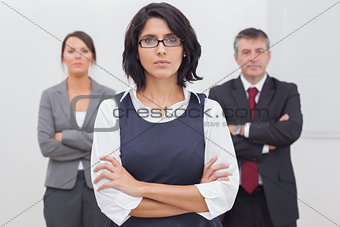 Three business people folding their arms seriously