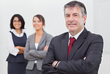 Businessman and his team smiling arms crossed