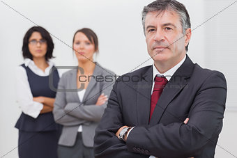 Businessman and his team standing with crossed arms