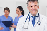 Doctor with stethoscope smiling and his team behind him