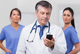 Doctor looking at phone with his team of nurses