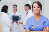Nurse standing seriously with her team