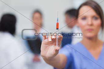 Nurse showing syringe