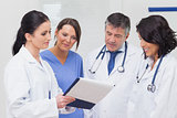 Nurse and doctors looking at clipboard