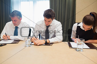 Business people taking notes at desk
