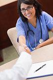 Happy nurse shaking doctors hand