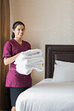 Smiling hotel maid holding towels