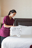 Hotel maid putting towels on bed