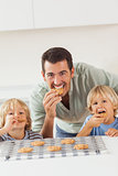 Father and his sons eating cookies