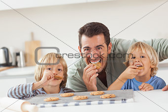 Smiling father and his sons eating cookies
