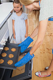 Mother and her daughter taking cookies from the oven