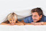 Smiling father and his son lying under the duvet