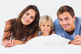 Family lying on a bed together