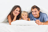 Family smiling under the duvet