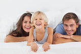 Happy family lying on a bed together