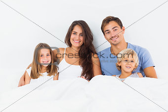 Cheerful family lying on a bed together