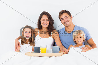 Family taking the breakfast on the bed