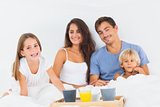 Happy family taking the breakfast on the bed