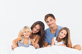 Happy family posing on the bed