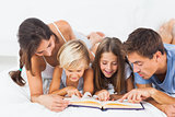 Family reading a book on the bed