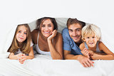 Happy family in the duvet smiling